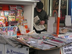 elderly man watching over newspaper stand
