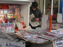 elderly man watching over newspaper stand